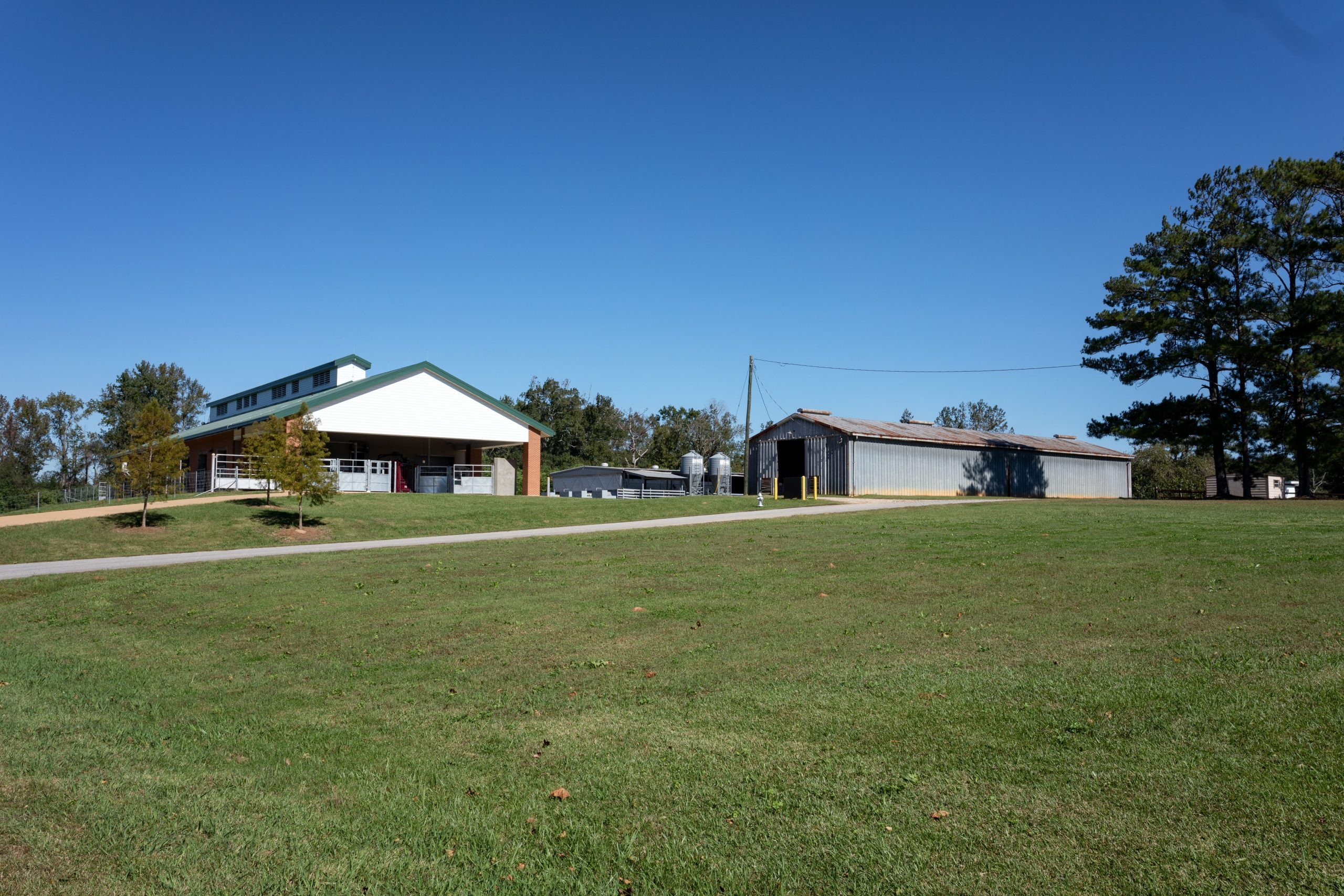 Driveway leading to red brick barn and two silver metal rectangular buildings